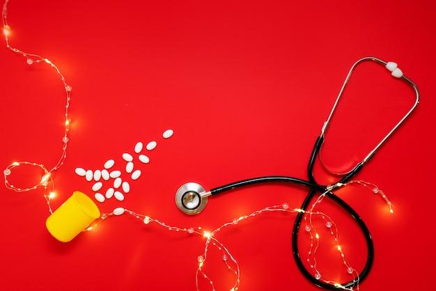 청진 기의 아름 다운 화 환과 빨간색 배경에 의료 레이아웃 알 약으로 만든 크리스마스 트리. 의사와 의료 클리닉을 위한 메리 크리스마스 컨셉입니다.