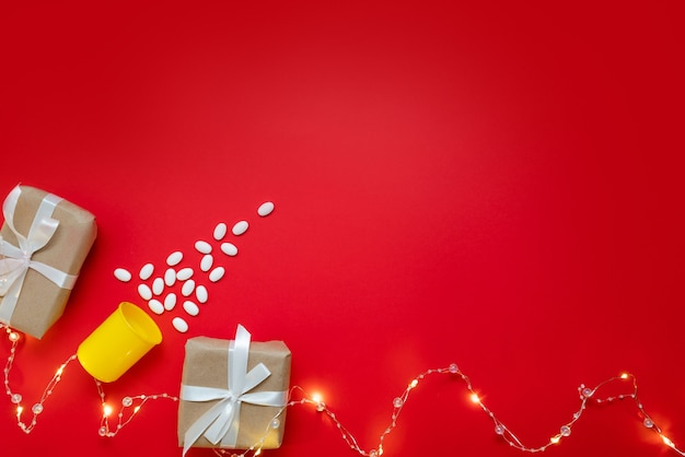 Medical layout on a red background with a beautiful garland of a christmas tree made of pills and gifts. merry christmas concept for doctors and medical clinics
