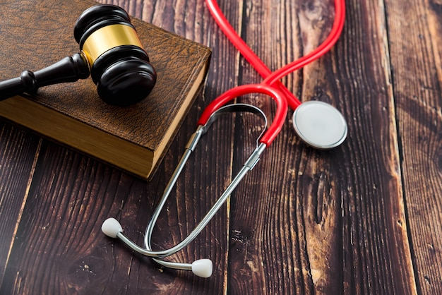 Medical malpractice and errors makes doctors and patients go to court, gavel on legal books.