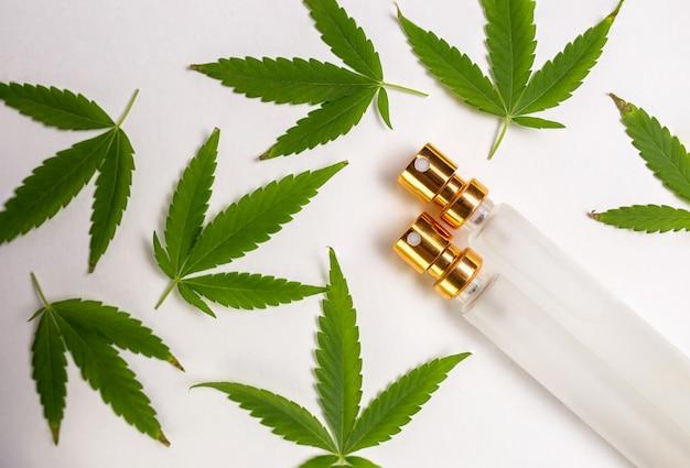 흰색 배경에 의료용 마리화나 잎과 유리병
