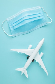 Medical mask against coronavirus with airplane on blue background. travel concept. top view