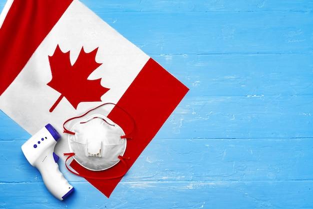 캐나다 국기에 의료 마스크와 비접촉식 온도계