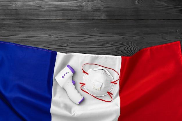 의료 마스크와 나무 테이블에 프랑스의 국기에 비접촉식 온도계