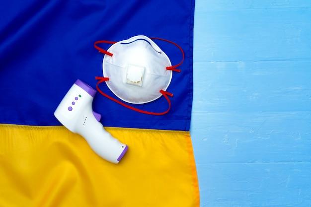 의료 마스크 및 나무 보드에 우크라이나의 국기에 비접촉식 온도계