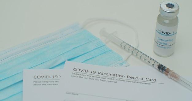 Медицинская маска и вакцина против covid-19 в карте прививок, одобренных cdc, с флаконами с вакциной против вируса короны.