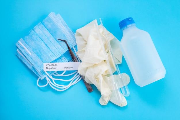 Медицинская маска и дезинфицирующее средство на синей поверхности
