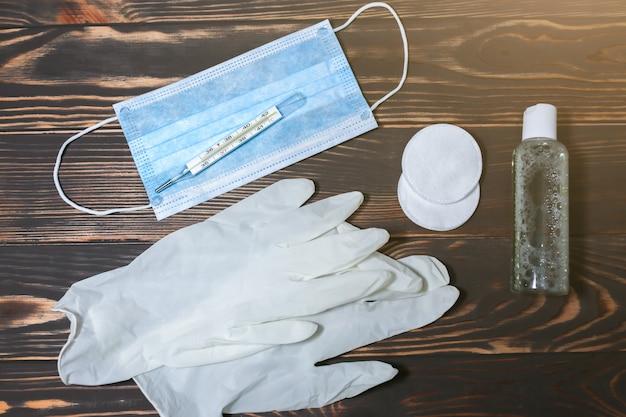 Медицинская маска и ртутный термометр. антисептик и ватные диски с резиновыми перчатками. вирусная болезнь. опасность пандемии коронавируса. грипп и простуда зимой. высокая температура и симптомы кашля.