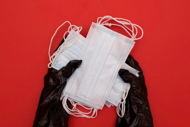 医療用マスクと赤の消毒剤。コロナウイルス予防医療サージカルマスクと手指衛生コロナウイルス保護のための手指消毒剤。コロナウイルスcovid-19検疫による危機。