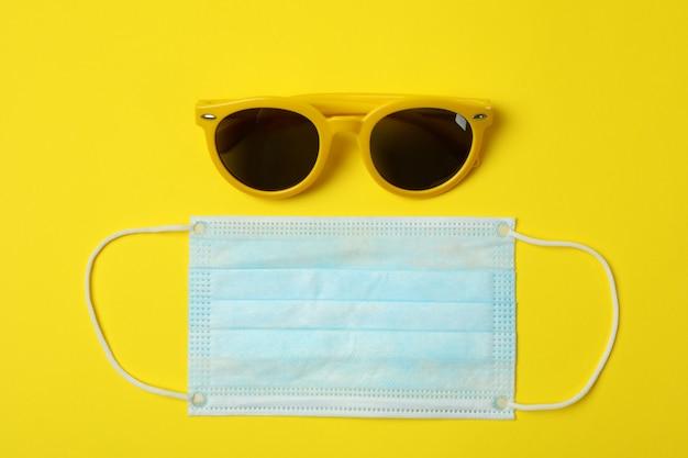 Медицинская маска и солнцезащитные очки на желтом фоне