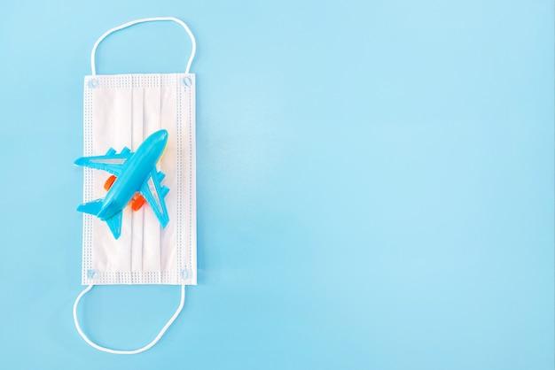 파란색 배경에 의료 마스크와 장난감 비행기. 공간을 복사합니다.