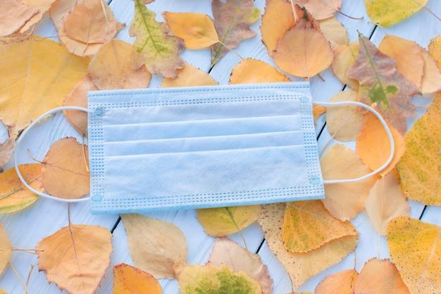 Медицинская маска осень на фоне осенних листьев. концепция covid, респираторные заболевания, защита