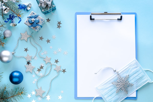 Medical mask, blank clipboard and christmas decorations