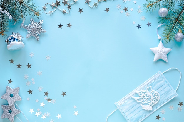 Medical mask and christmas decorations on blue surface