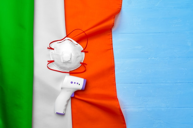 Medical mask and contactless thermometer on flag of italy