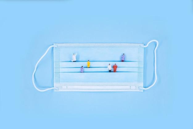 코로나 바이러스에 대한 의료 마스크. 많은 사람들과 의료 보호 마스크는 파란색 배경에 그림. 의료 의료 코로나 바이러스 검역, 위생 개념.