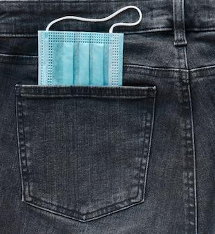 Medical mask in jeans pocket