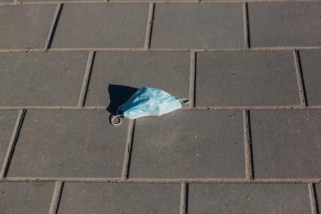 地面に横たわっている医療用マスク、路上で廃棄された医療用マスク、街路汚染、都市