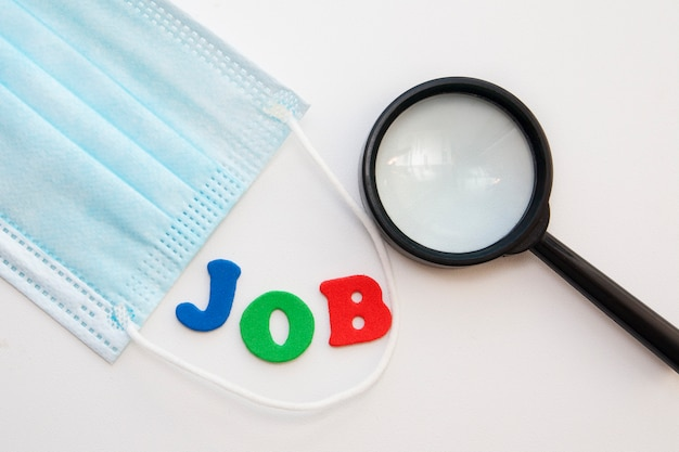 Medical mask and a magnifying glass near the word job done with letters