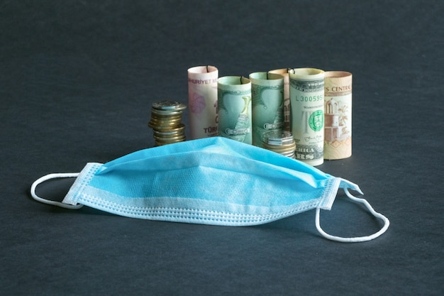 A medical mask and money. pandemic and the economic crisis of the concept