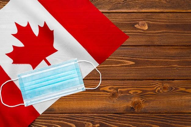 木の板にカナダの旗の医療マスクをクローズアップ