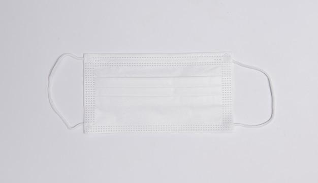 白い表面の医療用マスクは、コピースペースのある上面図を平らに置きます。ウイルス、コロナウイルス、インフルエンザ、風邪、病気に対する保護。伝統的な医療ツール、健康の概念。医学的背景