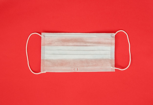 Medical mask on a red background, minimalism.