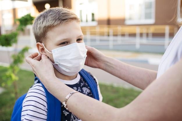 コロナウイルスを防ぐための医療用マスク。母は息子の顔に防塵マスクをかけます。学校に戻る