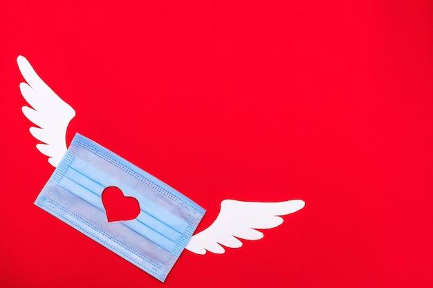 Медицинская маска с резным сердцем и крыльями ангела. день святого валентина и концепция коронавируса.