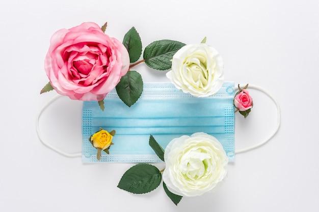 白に異なる色の花を持つ医療用マスク。