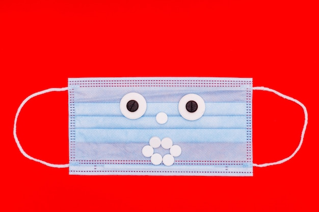 Medical mask with a face made of pills on a red background