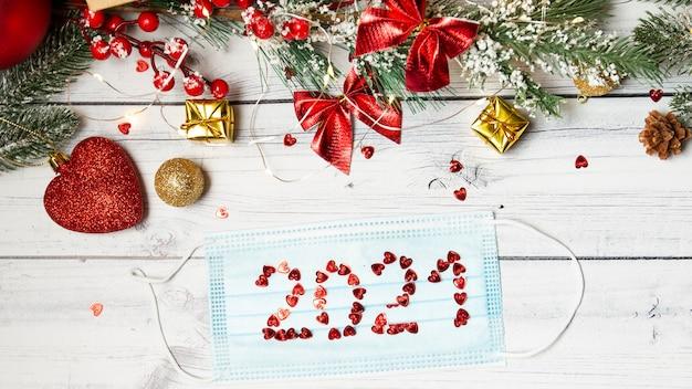 Медицинская маска с номером 2021 и елочными украшениями. рождество в условиях пандемии коронавируса