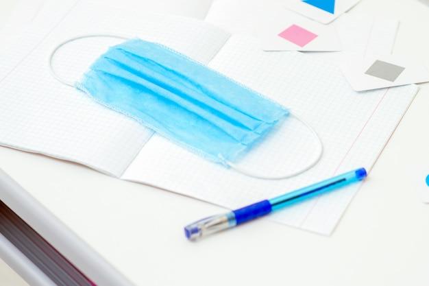 Медицинская маска с ручкой над тетрадью.