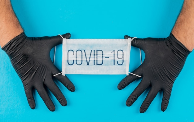 Medical mask with text covid-19 in a hands with black gloves top view