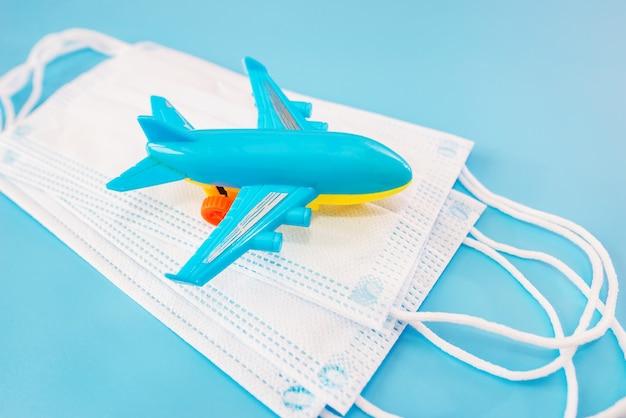 파란색 배경에 의료 마스크와 장난감 비행기. 확대.