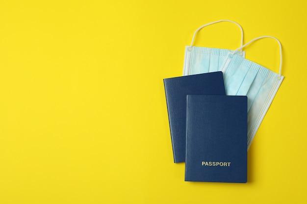 黄色の背景に医療用マスクとパスポート