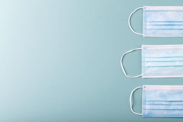 Медицинские маски на синем фоне текстуры. covid-19. вид сверху. скопируйте пространство.