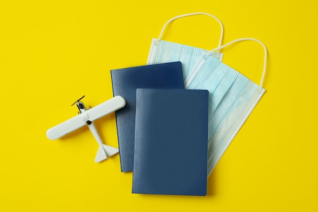 Medical masks, passports and toy plane on yellow background