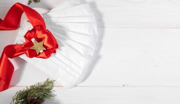 Медицинские маски с бантом из ленты в качестве рождественского подарка на белом, коронавирусном новогоднем фоне