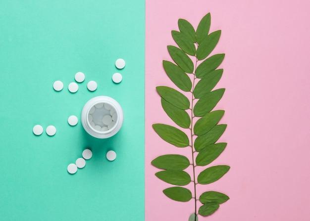 Медицинский минималистичный натюрморт. бутылка с таблетками, веточка с зелеными листьями на пастельном фоне.
