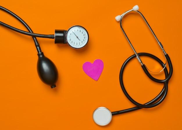Medical monometer, stethoscope, decorative heart on orange background