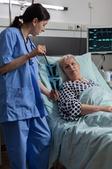 Medical nurse analyzing senior patient chest xray in hospital room