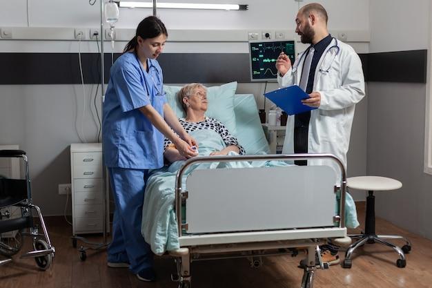 그녀가 oxygem 마스크의 도움으로 호흡하는 동안 의사와 진단 및 치료에 대해 논의하는 병원 침대에 누워 노인 여성 환자에 산소 측정기를 부착하는 의료 간호사