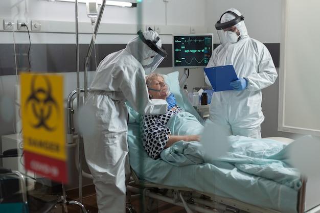 Медицинская медсестра, одетая в костюм ppe, надевает кислородную маску пожилому пациенту во время глобального панд ...