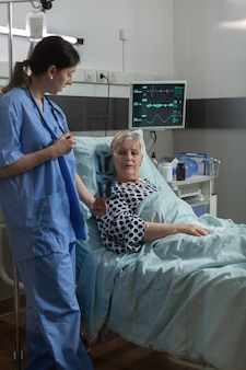 Medical nurse explaining chest x-ray radiography to elderly patient, breathing with help from oxygen mask because of respiratory illness