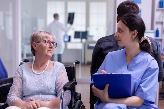 Medical nurse explaining diagnosis to handicapped senior woman patient