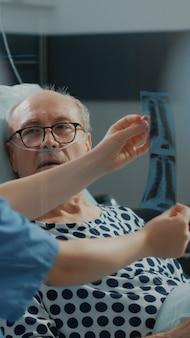 아픈 환자에게 엑스레이 결과를 설명하는 의료 간호사