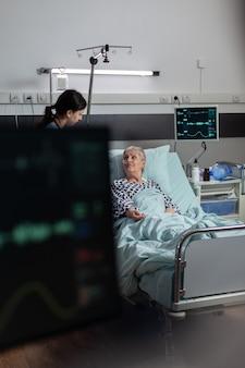 노인 여성 환자에게 연민을 보여주는 수술 용 의료 간호사, 산소 마스크의 도움으로 호흡하는 병원 침대에 누워 iv 드립 백에서 정맥 주사 약 받기