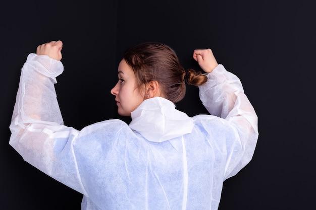 흰색 의료 제복을 입은 의료 간호사가 카메라를 향해 포즈를 취한 주먹을 꽉 쥐고 손을 들어 올립니다.