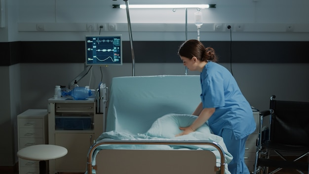 Medical nurse organizing blanket and pillow on hospital bed in clinical ward for treatment emergency...