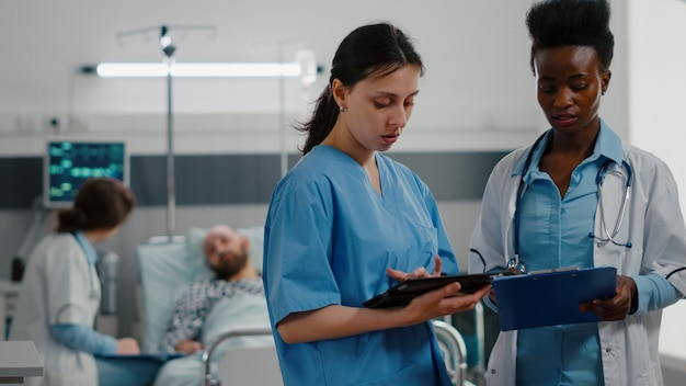 Medical nurse showing medical expertise using tablet computer to specialist black doctor woman
